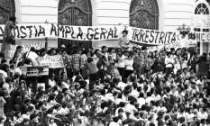 """Em 1979, na escadaria da Câmara dos Vereadores, na Cinelândia, manifestantes seguram uma faixa onde se lê """"Anistia ampla, geral e irresitrita"""" Foto: Terceiro / Infoglobo"""