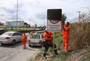 Enquanto placas não são retiradas, agentes a cobrirão com sacos pretos Foto: Gabriel Esteves / DER-RJ / Divulgação