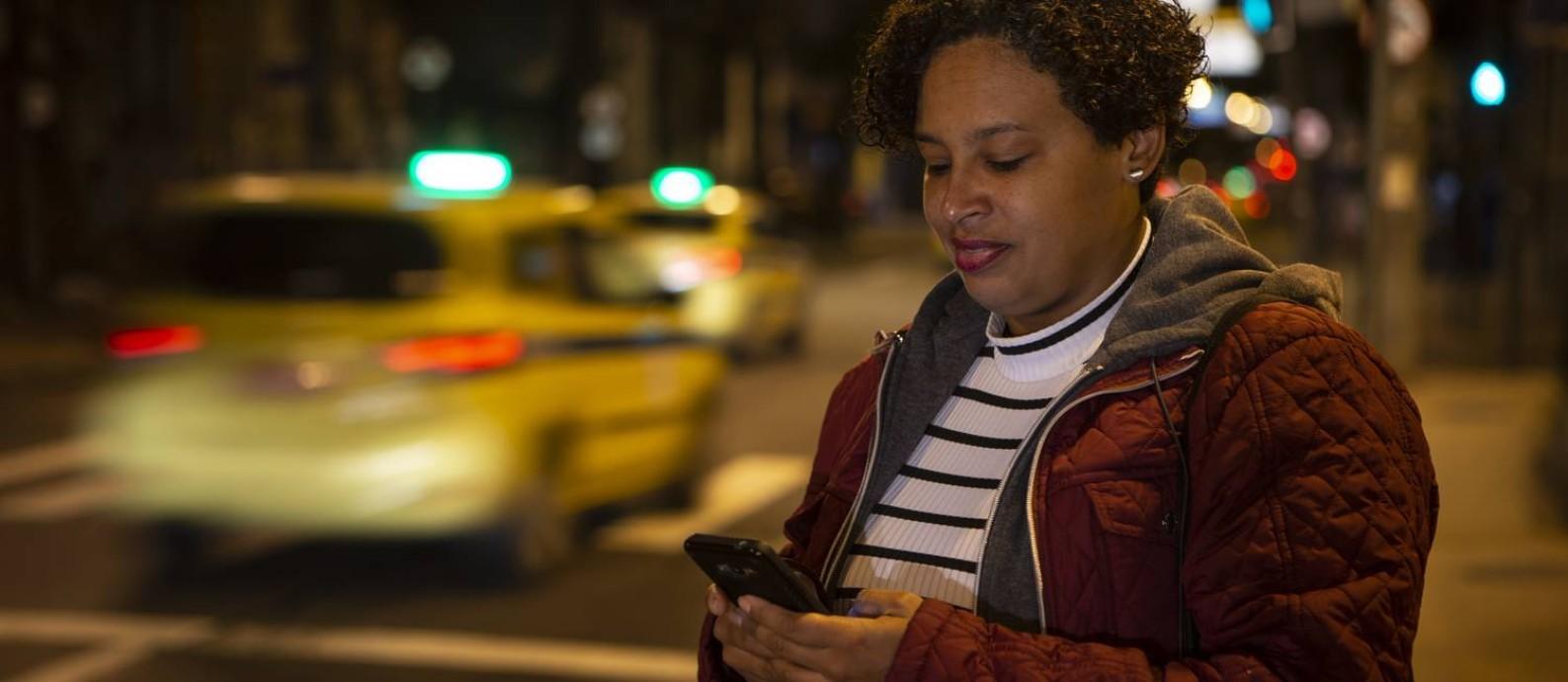 A universitária Priscila espera um motorista de aplicataivo: uma só viagem de carro em vez de pegar um ônibus e o VLT Foto: Alexandre Cassiano / Agência O Globo