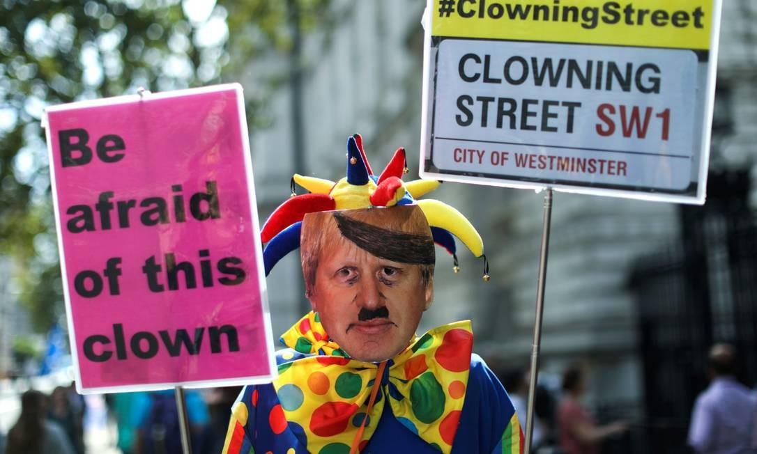 Homem com roupa de palhaço e máscara de Boris Johnson carrega placas contra premier Foto: SIMON DAWSON / REUTERS
