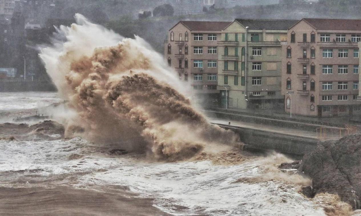 Ondas atingem um paredão em frente a edifícios em Taizhou, província de Zhejiang, leste da China. Os mesmos oceanos que nutriram a evolução humana estão prontos para desencadear a miséria em escala global alerta um projeto de relatório da ONU Foto: - / AFP