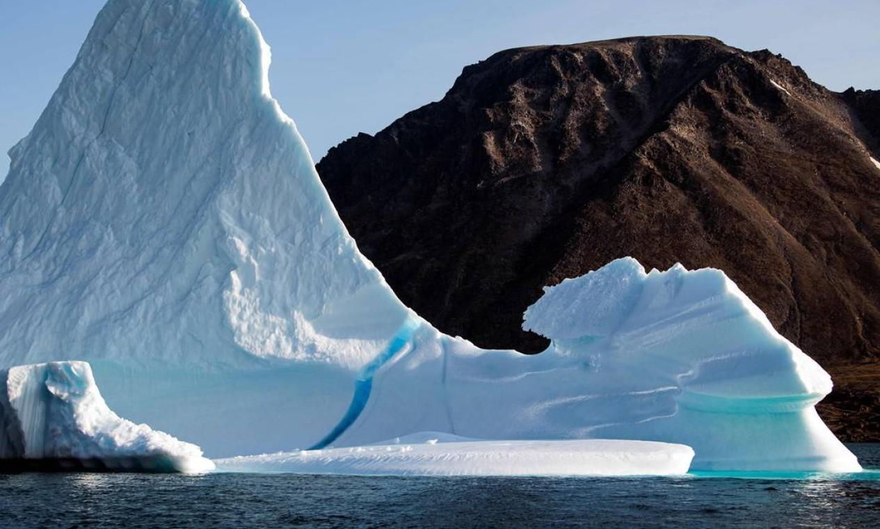 Iceberg perto da ilha de Kulusuk, na costa sudeste da Groenlândia. Aquecimento global causado pelas atividades humanas terá consequências dramáticas para os oceanos e a criosfera, que inclui gelo marinho, geleiras, calotas polares e permafrost (tipo de solo encontrado na região do Ártico, constituído por terra, gelo e rochas permanentemente congelados) Foto: JONATHAN NACKSTRAND / AFP