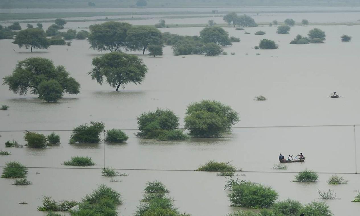 Moradores usam barcos para atravessar um rio Ganges inundado, à medida que os níveis de água nos rios Ganges e Yamuna aumentam, em Allahabad, Índia. Relatório do IPCC diz que chuvas de monção do verão indiano, uma fonte vital para regar as culturas destinadas a alimentar centenas de milhões de pessoas, enfraqueceram significativamente desde 1950, provavelmente devido ao aquecimento do Oceano Índico Foto: SANJAY KANOJIA / AFP