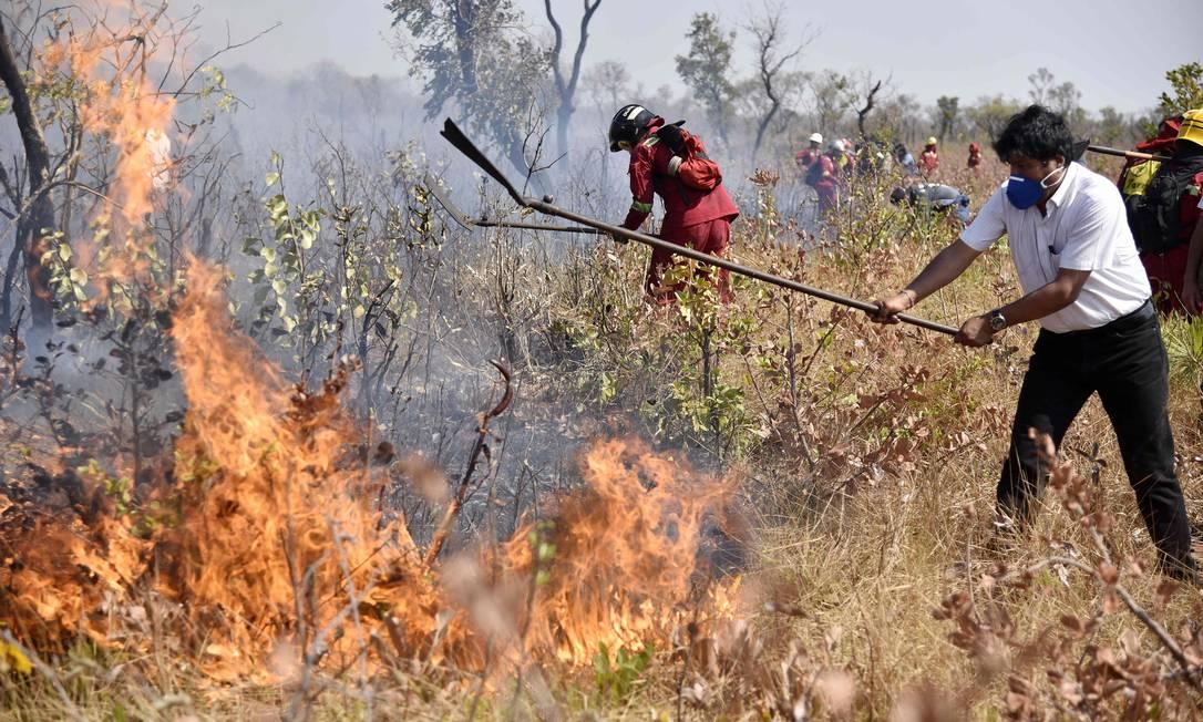 O presidente boliviano, Evo Morales, ajuda bombeiros a conter as chamas em Charagua, na fronteira com o Paraguai Foto: AIZAR RALDES / AFP