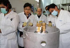 Inspetores da Agência Internacional de Energia Atômica e técnicos iranianos desconectam uma das centrífugas da central de Natanz, responsáveis por enriquecer urânio acima de 20%, em 2014 Foto: KAZEM GHANE / AFP