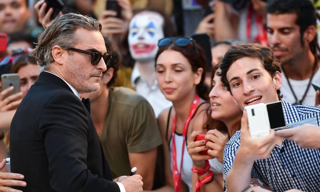 """Joaquin Phoenix posa para selfie na chegada de uma sessão de """"Coringa"""", em Veneza Foto: ALBERTO PIZZOLI / AFP"""