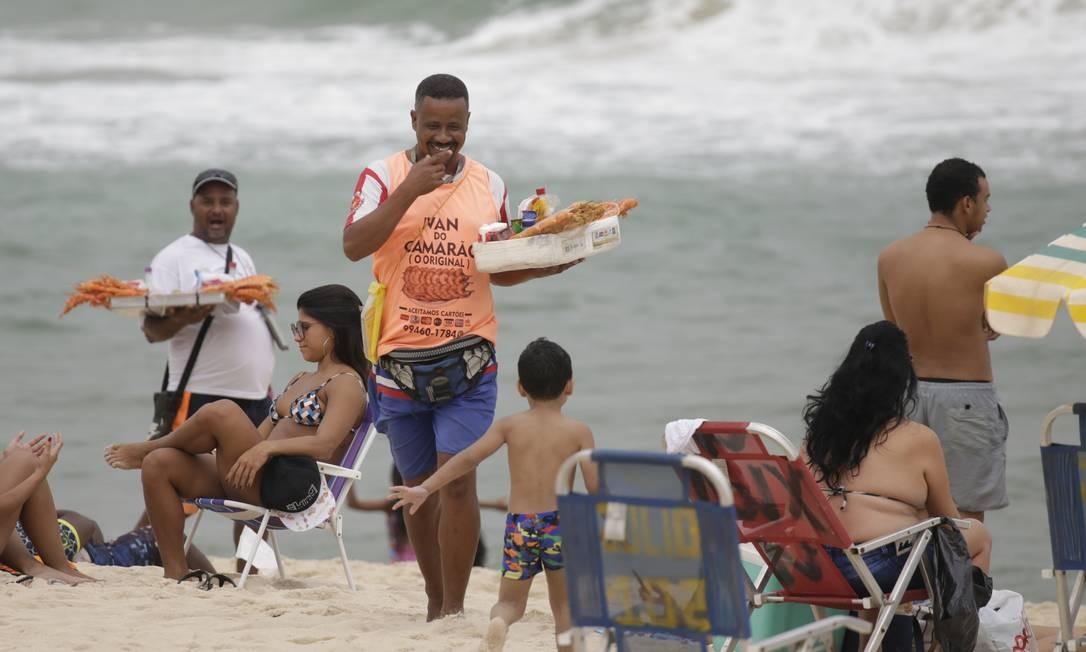 Ambulante vende espetinhos de camarão em Ipanema: atividade é considerada ilegal pelo código Foto: Gabriel de Paiva / Agência O Globo