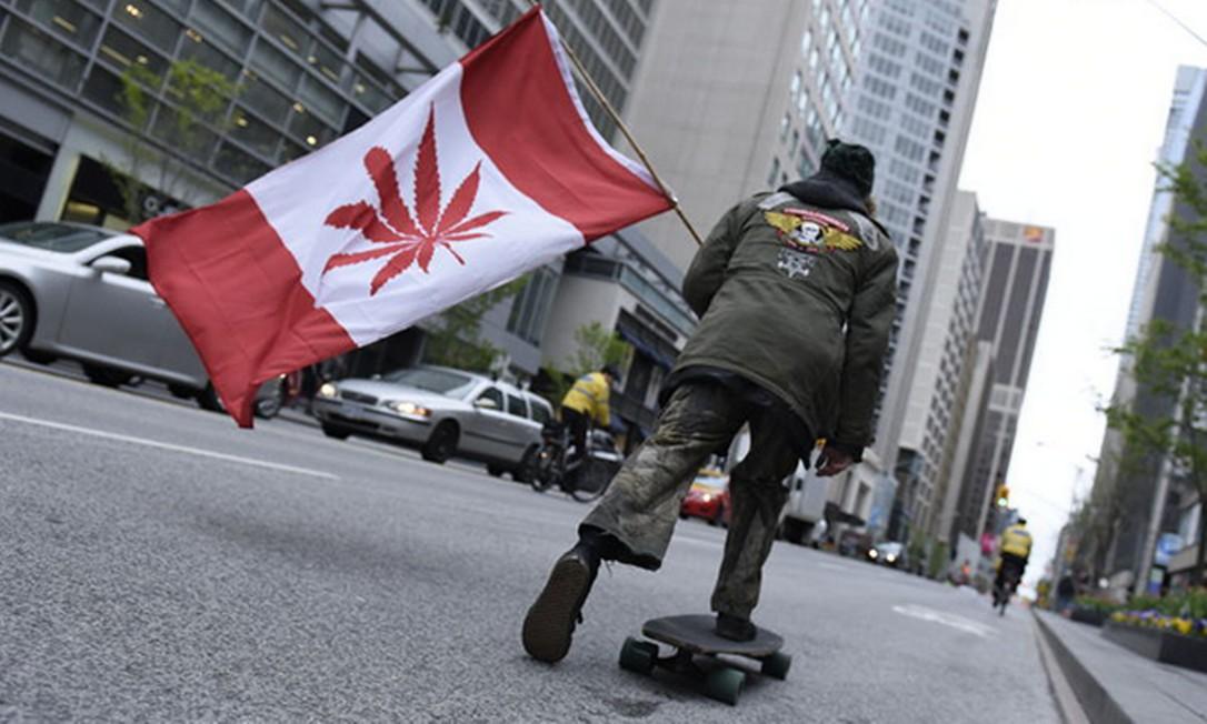 Homem anda de skate com uma réplica da bandeira canadense alterada para que a flor da Cannabis apareça como símbolo Foto: Arindam Shivaani / NurPhoto via Getty Images
