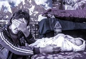 """Nyo, de 17 anos e vítima do tráfico de mulheres de Mianmar para a China, com o bebê que fruto do casamento e das relações sexuais forçadas com o """"marido chinês"""" Foto: MINZAYAR OO / NYT"""