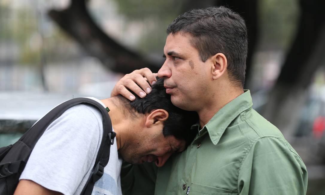 Os irmãos de José Pio Baía Junior aguardam liberação do corpo do pedreiro: Josemar (à esquerda) chora abraçado a Jorge Foto: Marcia Foletto / Agência O Globo