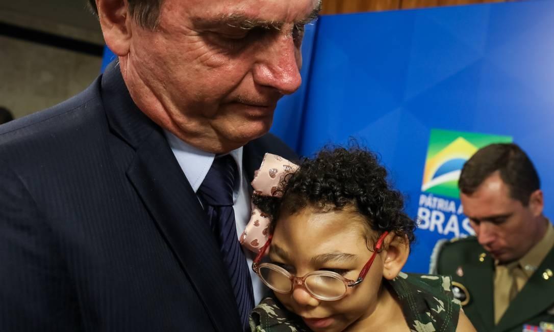 O presidente Bolsonado segura criança durante solenidade que garante pensão vitalícia para vítimas de microcefalia decorrente do vírus da zika Foto: Marcos Correa / Agência O Globo
