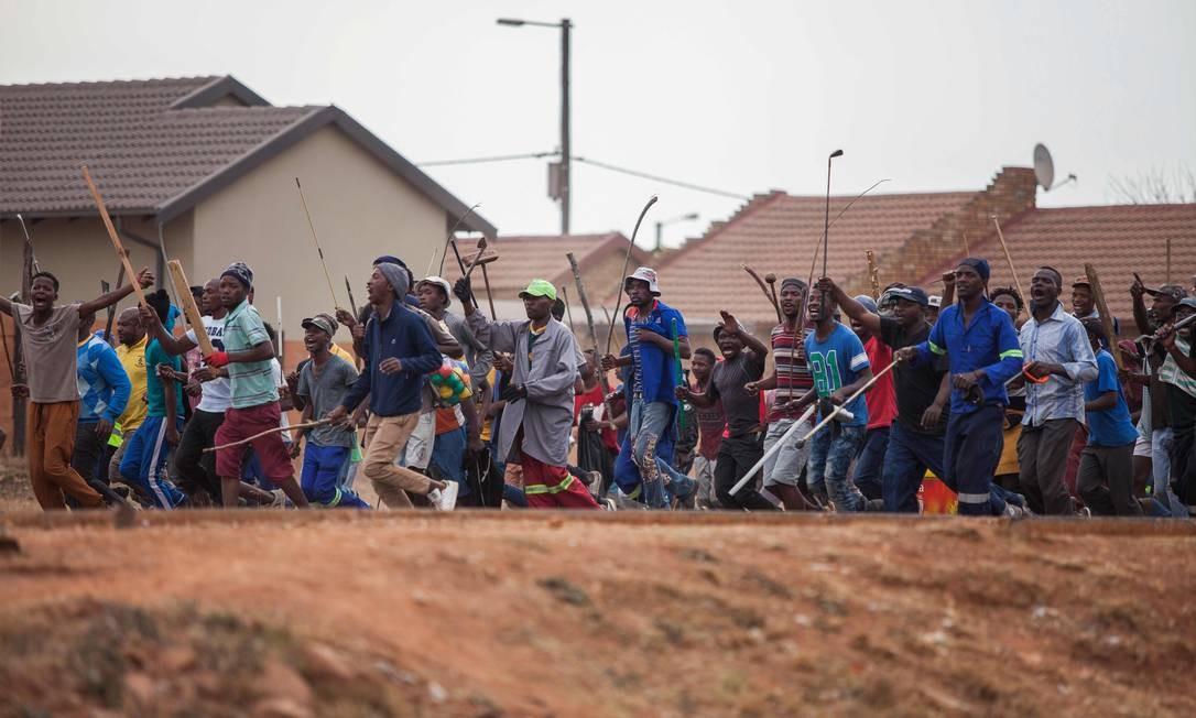 Multidão armada com pedaços de paus e machadinhas em um protesto contra a presença de imigrantes na periferia de Joanesburgo. 10 pessoas morreram em ataques xenofóbicos na África do Sul nos últimos dias Foto: GUILLEM SARTORIO / AFP