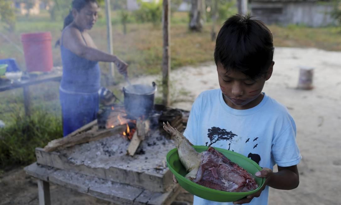 Menino com carne de caça em comunidade indígena na Bolívia Foto: Domingos Peixoto / Agência O Globo