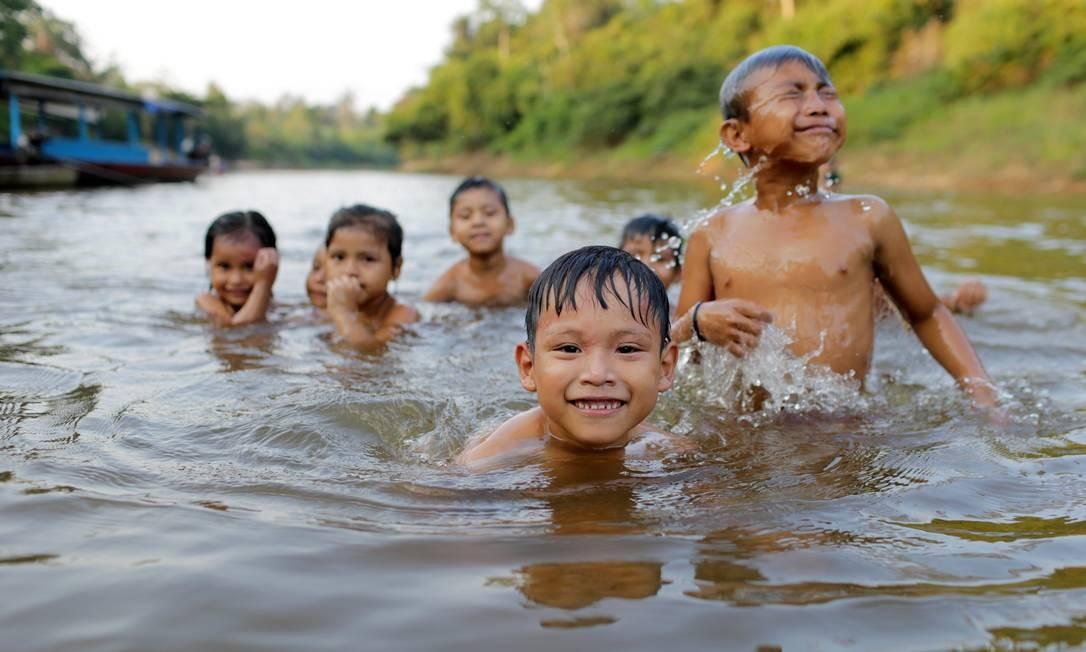 Crianças brincam em rio na comunidade das Mercedes Foto: Domingos Peixoto / Agência O Globo