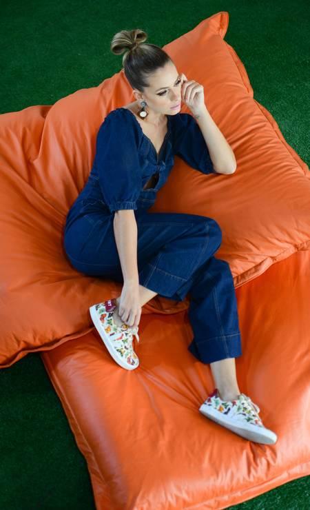Macacão Eco Refarm Jeans, R$ 498, Farm (99520-0392); tênis estampado, R$ 248, Vert; e brincos de madeira e madrepérolas, R$ 396, Fiszpan (2547-4818) Foto: Felipe Dahrlan