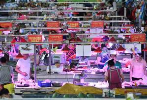 Vendedores de carne de porco em um mercado na China Foto: China Stringer Network / Reuters
