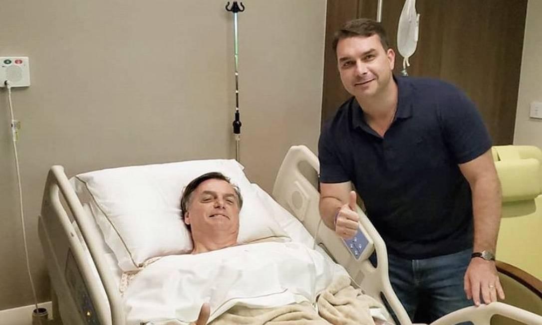 Bolsonaro e o filho Flávio após o presidente fazer a quarta cirurgia, desta vez, para corrigir uma hérnia provocada pelas outras operações Foto: Reprodução
