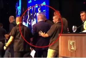 Momento em que o premier israelense, Benjamin Netanyahu, é retirado de palanque após alerta de ataque aéreo em Ashdod, no sul do país Foto: Reprodução de vídeo