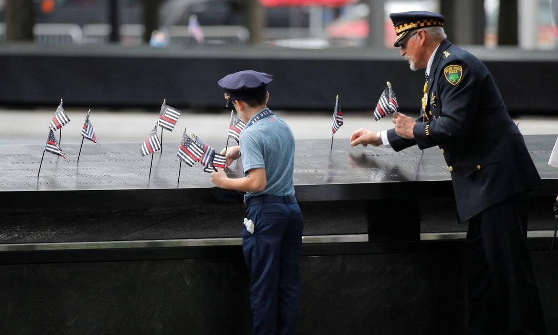 Pessoas colocam bandeiras onde estão gravados os nomes das vítimas do atentado, na beira do espelho d'água, em Nova York. Foto: BRENDAN MCDERMID / REUTERS