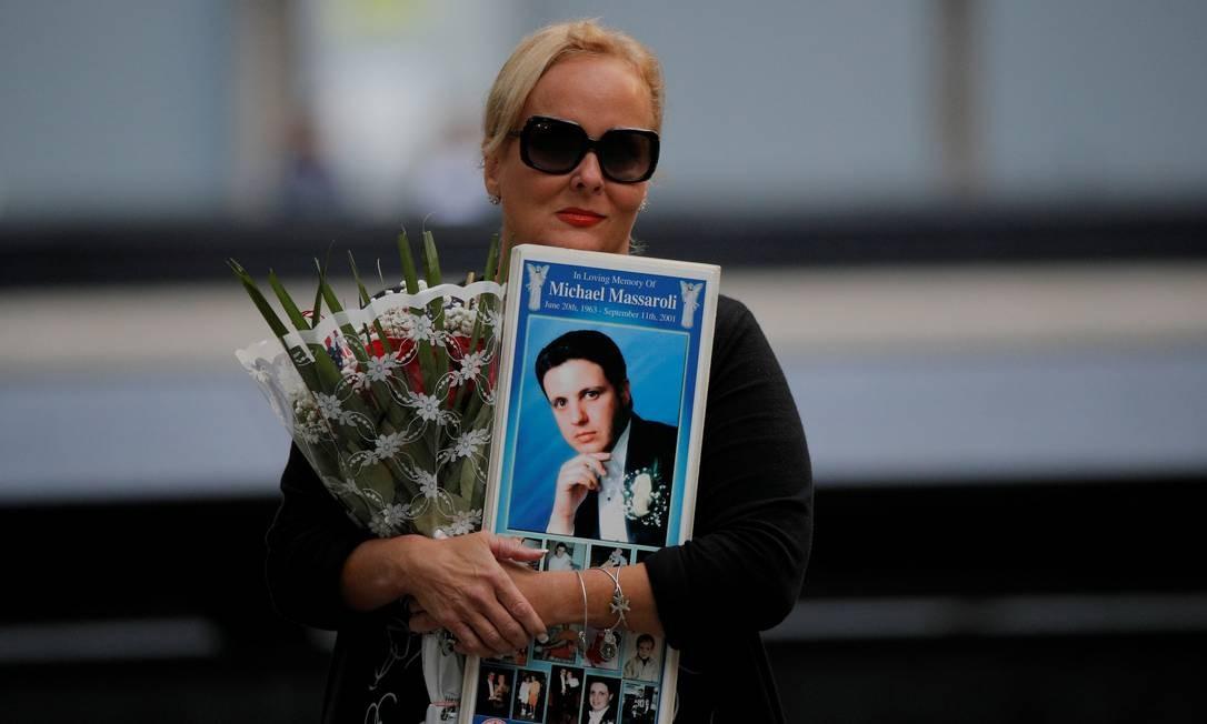Uma mulher carrega flores e o retrato de uma das vítimas do atentado. Foto: BRENDAN MCDERMID / REUTERS