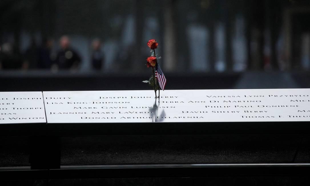 Flor e bandeira americana deixadas no Memorial do 11 de Setembro, em Nova York, EUA. Em todo o país, estão sendo realizadas cerimônias para lembrar as 2.977 mortes. Foto: BRENDAN MCDERMID / REUTERS