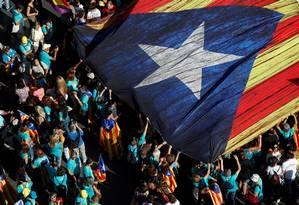 """Manifestam seguram uma gigantesca """"Estelada"""", a bandeira separatista da Catalunha, na manifestação desta quarta: polícia estimou comparecimento em cerca de 600 mil pessoas, contra mais de 1 milhão nos protestos de 2018 e 2017 Foto: ALBERT GEA/REUTERS"""