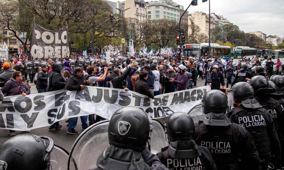 Manifestantes cercados pela polícia do lado de fora o Ministério do Desenvolvimento Social da Argentina no protesto desta quarta: organizações sociais prometem acampar no local enquanto esperam que governo decrete emergência alimentar Foto: DAMIAN DOPACIO/AFP