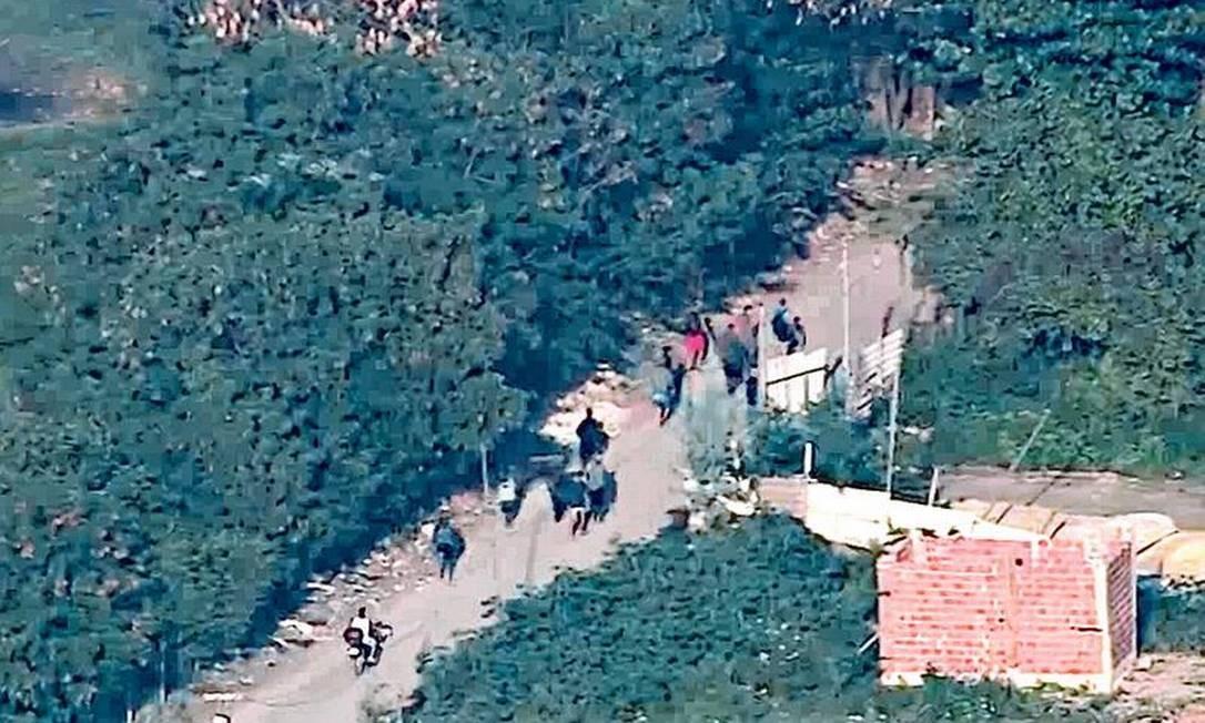 Traficantes deixam a Cidade de Deus pela trilha conhecida como Caminho do Outeiro: PM realizou operação na comunidade da Zona Oeste para retirar barricadas Foto: Reprodução / TV Globo