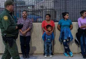 Agente de fronteira dos EUA vigia migrantes centro-americanos enquanto aguardam serem levados para centro de processamento em El Paso, Texas: restrições vão impedir que peçam asilo Foto: PAUL RATJE/AFP/16-05-2019