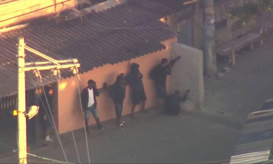 No mesmo dia, traficantes se esconderam atrás de um muro que havia sido derrubado pela policia e foi reconstruído pelos para ser usado como trincheira pelos bandidos Foto: Reprodução Tv Globo
