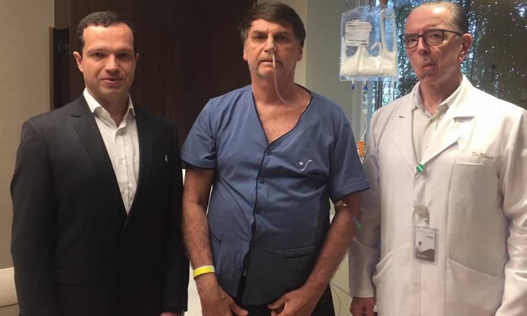 Bolsonaro ao lado dos médicos Luiz Henrique Borsato e Antônio Luiz Macedo Foto: Reprodução