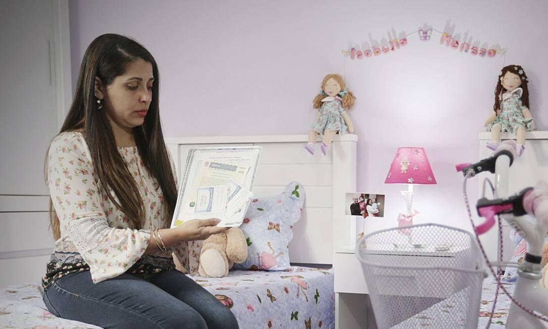 Cintia segura desenhos e documento de Registro de Nascimento no quarto que ela fez para as sobrinhas em sua casa no bairro Vila Emil em Mesquita Foto: Cléber Júnior / Agência O Globo