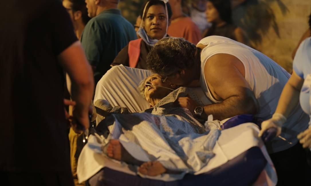 Pacientes são retirados do hospital. Alguns estavam em tratamento na CTI. A morte de um paciente já foi confirmada pelos Bombeiros Foto: Alexandre Cassiano / Alexandre Cassiano