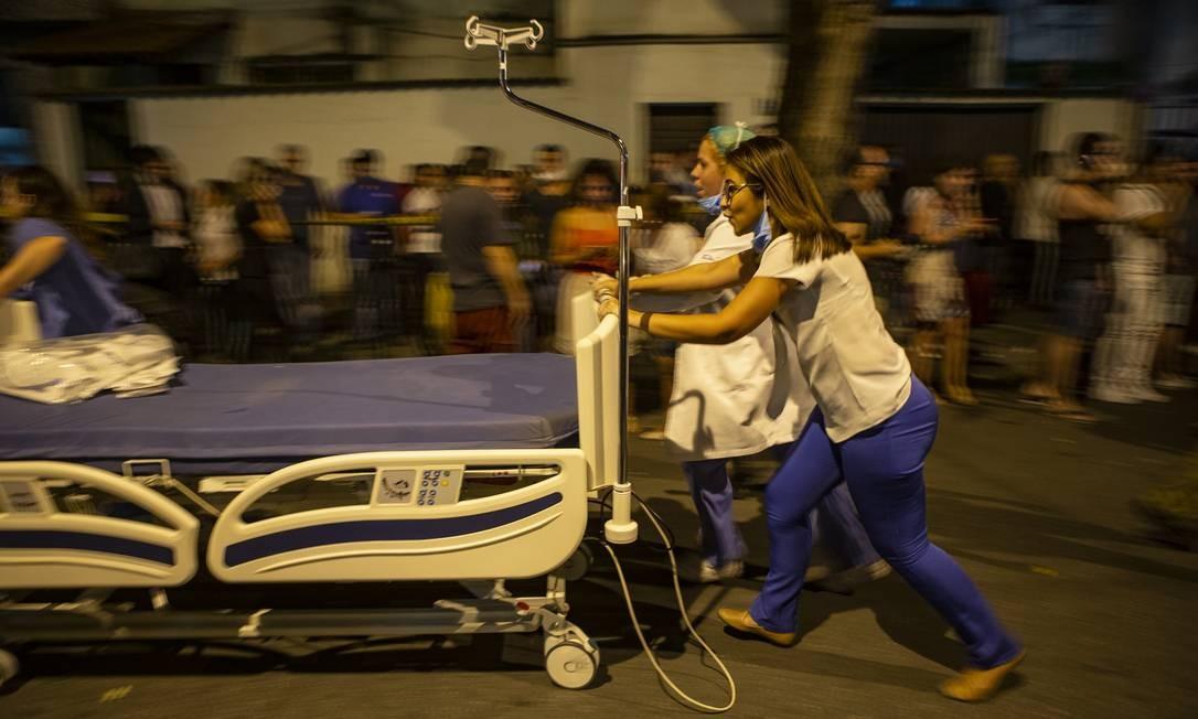 Funcionários levam cama hospitalar para acomodar paciente durante o inc~endio Foto: Alexandre Cassiano / Agência O Globo