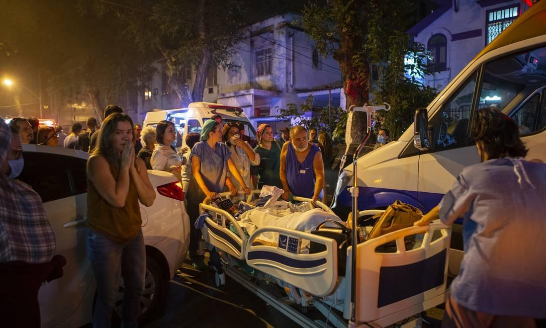 Equipe do hospital carregando pacientes que estavam na cama e não tinham como se levantar Foto: Alexandre Cassiano / Agência O Globo