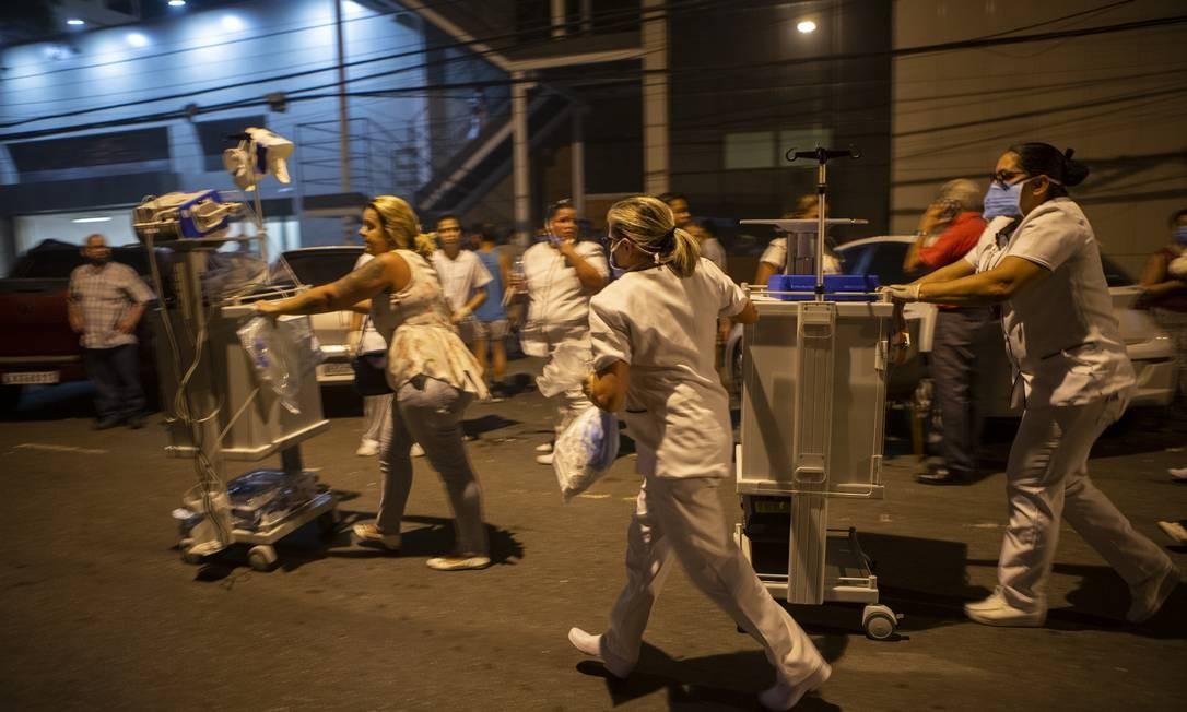 Desespero para salvar vidas, fuincionários correm com equipamentos necessários aos pacientes que foram retirados do hospital Foto: Alexandre Cassiano / Agência O Globo