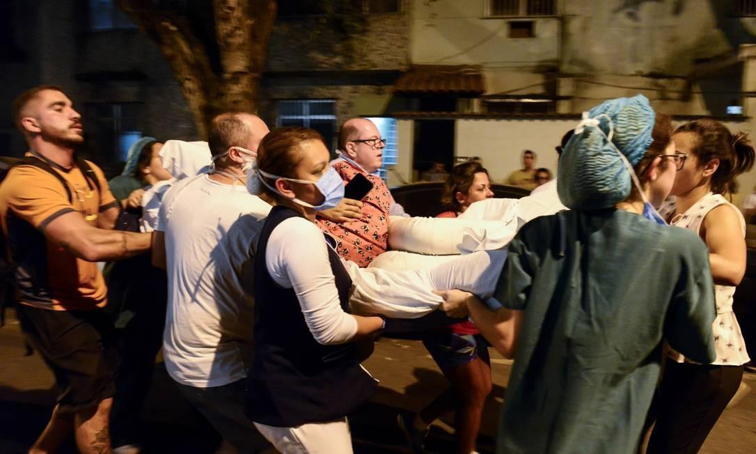Profissionais de saúde e vizinhos retirando paciente do Hospital Badim Foto: Celso Pupo / Fotoarena/Agência O Globo