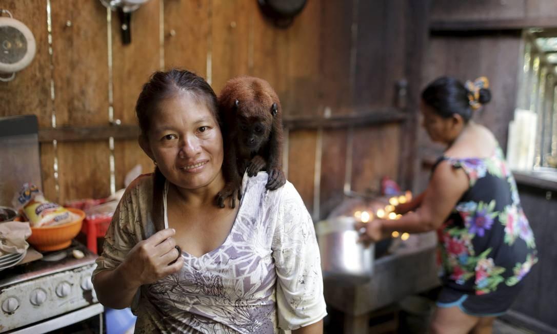Cozinheira na comunidade Tacana, na Amazônia boliviana, Lucena Cartagena com seu macaco Moracha Foto: Domingos Peixoto / Agência O Globo