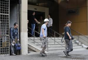 De camisa azul, membro da equipe de perícia sai com peça queimada de Hospital Badim Foto: Pablo Jacob / Agência O Globo