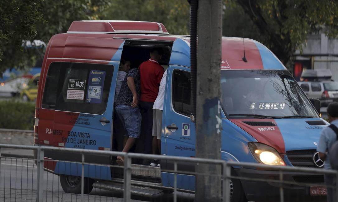 Pessoas embarcam na van já lotada no ponto da Leopoldina Foto: Marcelo Theobald