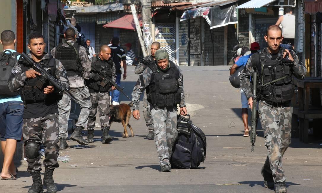 Policiais levam mala com drogas e armamento apreendida no Jacarezinho Foto: Fabiano Rocha / Agência O Globo