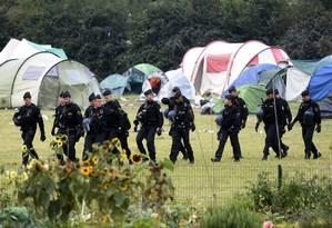 Policiais franceses circulam pelo acampamento de migrantes em Grande-Synthe, no Norte do país, no início do trabalho de desmantelamento do local nesta terça por ordem da Justiça Foto: FRANCOIS LO PRESTI/AFP