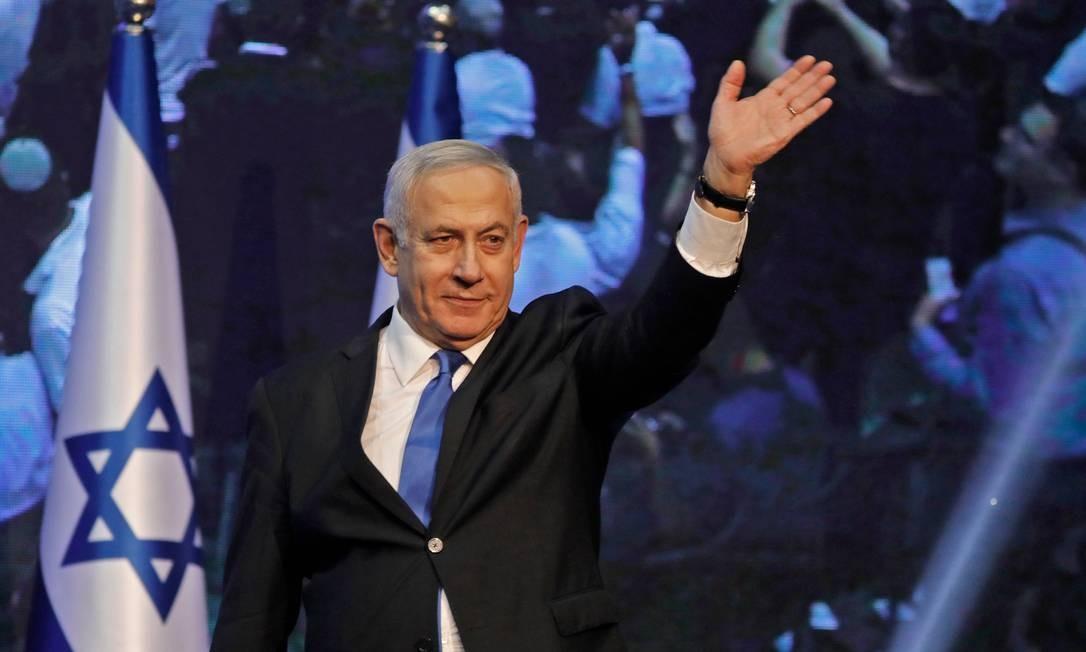 Premier israelense Benjamin Netanyahu acena a correligionários durante comício após as eleições gerais desta terça-feira. Projeções mostram que ele terá dificuldade para permanecer no cargo Foto: MENAHEM KAHANA / AFP