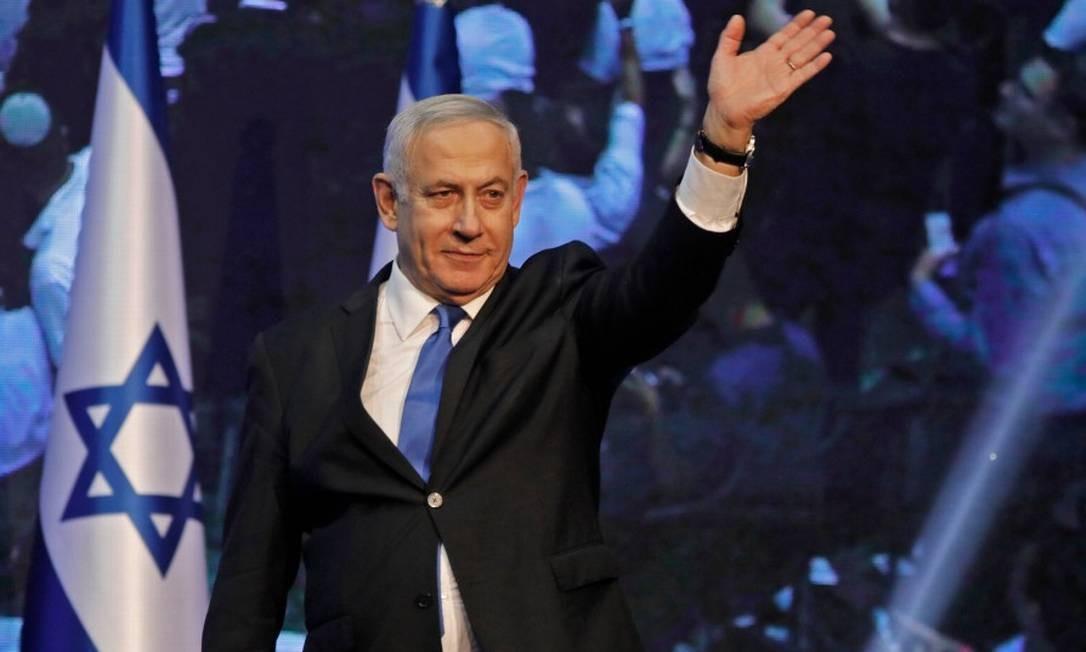 Primeiro-ministro Benjamin Netanyahu acena para apoiadores após discurso para seus apoiadores no quartel-general de sua campanha Foto: MENAHEM KAHANA / AFP