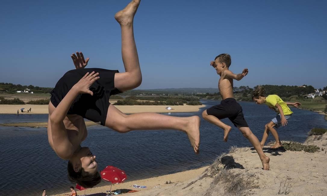 Crianças brincam na areia da Lagoa de Melides, no litoral do Alentejo, em Portugal Foto: Daniel Rodrigues / The New York Times