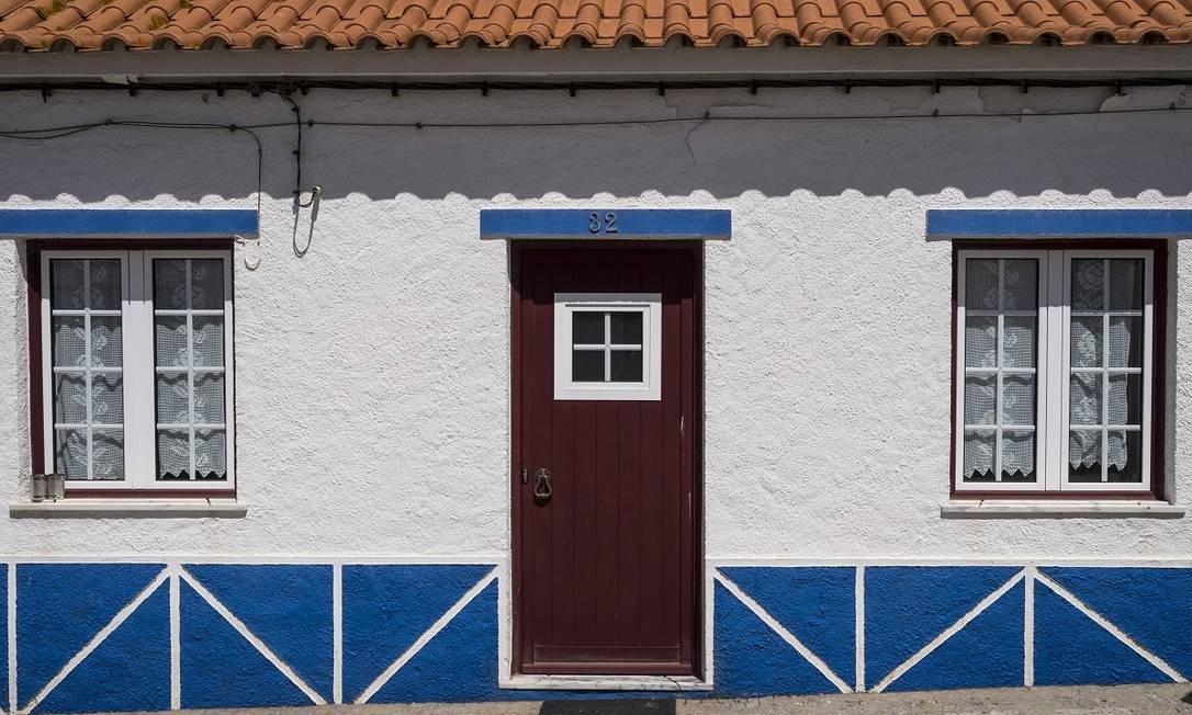 Uma casinha típica na rua principal de Porto Covo, um vilarejo de pescadores no litoral do Alentejo Foto: Daniel Rodrigues / The New York Times