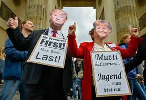 """No Portão de Brandemburgo, em Berlim, Alemanha, manifestantes com máscaras do presidente dos EUA, Donald Trump, e da chanceler alemã, Angela Merkel, exibem cartazes dizendo """"Sr. Presidente Primeiro, Sra. Earth Last"""" (E) e """"Mutti (Mãe, que significa Merkel) vocês não conseguiram, os jovens precisam consertar"""" no protesto """"Sextas-feiras para o futuro"""" contra mudanças climáticas Foto: JOHN MACDOUGALL / AFP"""