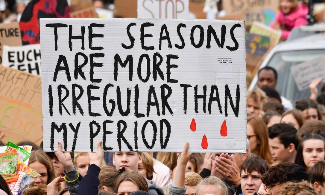 """Um manifestante segura cartaz com a inscrição """"As estações são mais irregulares do que a minha menstruação"""" durante a manifestação no Portão de Brandemburgo, em Berlim Foto: JOHN MACDOUGALL / AFP"""