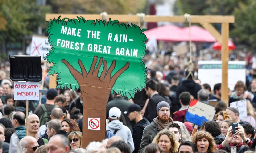 Manifestantes seguram uma placa em forma de árvore com a mensagem