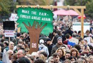 """Manifestantes seguram uma placa em forma de árvore com a mensagem """"Torne a floresta tropical novamente grande"""" durante a manifestação """"sextas-feiras para o futuro"""" no Portão de Brandemburgo, em Berlim Foto: JOHN MACDOUGALL / AFP"""